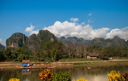 Temporary building on the banks of the river for vacations in front of mountains and clear sky.