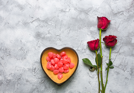 Red roses placed in a bowl of red heart-shaped candy on a gray-white surface with a copy space for the Valentine's Day festival. Reklamní fotografie