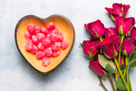 Many heart shaped candy Packed in a heart-shaped wooden cup With a bouquet of roses Placed on blue-white surface.