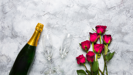 A bottle of champagne with a glass, placed on the side of group of red roses On the surface of white and gray With copy space For the Valentines Day festival Reklamní fotografie