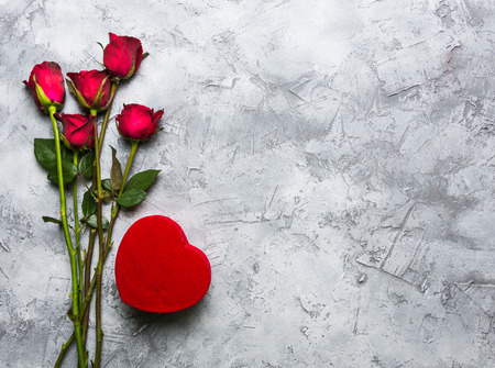Red rose, similar to a red heart-shaped gift box on a gray-white surface with coppy space  For Valentine's Day. Reklamní fotografie - 120780879