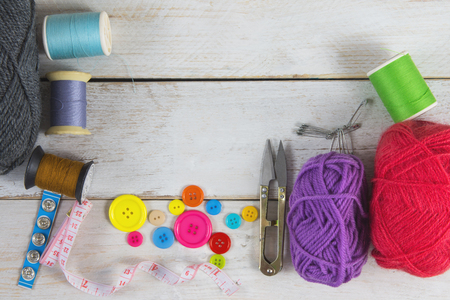 Sewing and crafting Includes thread, yarn, button, scissors, measuring tape and brooch. Placed on a white vintage wooden floor.
