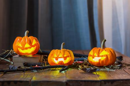 Drei orangefarbene Kürbisse, die für das Halloween-Festival in ein Geistergesicht geschnitzt wurden. Mit den Ästen und Stroh auf den alten Holzboden legen.