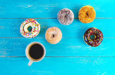 Donut coated with coconut,nuts and cream, Appetite. Layered on a wooden floor in vintage blue. with a cup of black coffee. Reklamní fotografie - 120773887