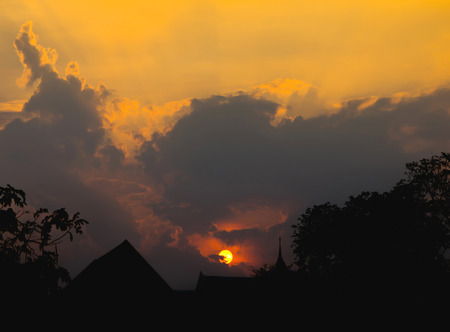 Silhouet image of the top of the building with Thai architecture in front of sunset and the beautiful clouds of yellow and orange. Reklamní fotografie