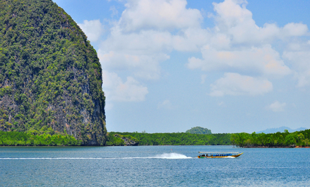 A medium-sized cruise ship is sailing on blue water behind a large rocky hill. Reklamní fotografie