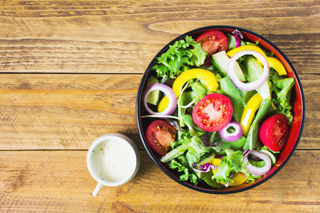 Salads include green oak, lettuce, tomato, yellow pepper, avocado and onion. Side by side with a cup of sesame dressing. Lay on a brown vintage wood floor. Reklamní fotografie - 120774457
