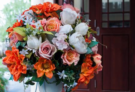 A fake flower bouquet made of plastic arranged in a white pot. Reklamní fotografie