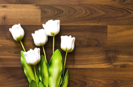 Bright white fake tulip made of plastic, placed on a tile floor, patterned dark brown wood.