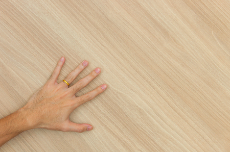 The man's left hand carries a gold ring on his finger on a wooden floor.