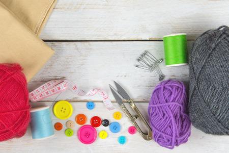 Cucito e lavorazione Include filo, filato, bottone, forbici, metro e spilla. Posizionato su un pavimento in legno vintage bianco.