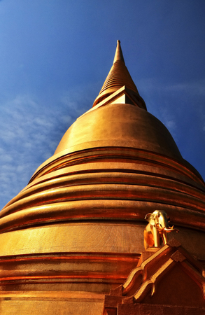 The large Buddhist pagoda in Thailand is adorned with elephant statues and golden mosaic tiles. Reklamní fotografie