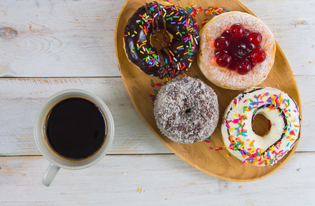 Donut coated with various toppings. Contains white and dark chocolate, nuts, jelly and Icing sugar sliced in a wooden tray, paired with one black coffee cup. On a white vintage wooden table.