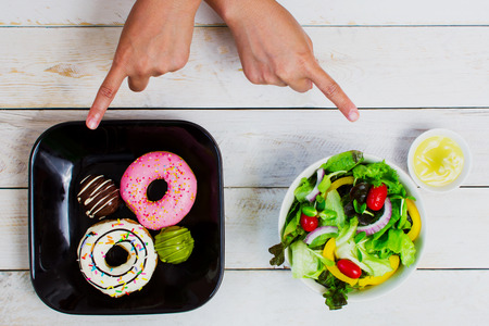 Donut coated with cream, strawberry and chocolate, placed on a black ceramic plate. Pair with vegetable salad in white ceramic bowl with cream dressing, There are hand gestures to choose from. All are on a vintage white wood floor. Reklamní fotografie - 120773875