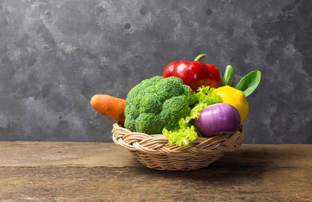 Various kinds of vegetables Consisting of carrots, lemon, bell peppers, broccoli, tomatoes, onions, choy, lettuce, pasta All placed in a wicker basket Placed on an old wooden floor with a grey wall in the background and copy space. Reklamní fotografie - 134763685