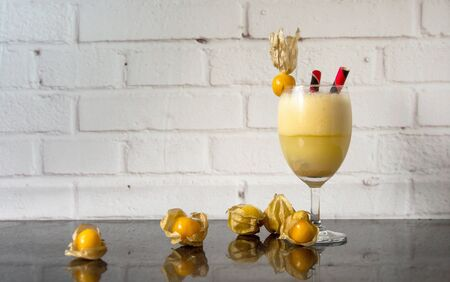 Cape gooseberry smoothie juice, packed in beautiful glass decorated with fruit and wafers stick placed on a black shiny stone tabletop. Reklamní fotografie - 134763688