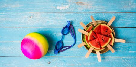 Watermelon cut into pieces Plugged in with a stick, making it like ice cream, stacked in a side dish with swimming goggles and ball for water activities. Is an item for the summer time to cool off All placed on a vintage blue wooden background. Reklamní fotografie - 134763689