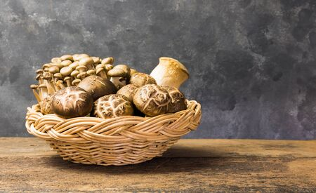 3 types of Japanese mushrooms for cooking food that is highly beneficial to the body, such as Orrinji mushrooms, Shiitake mushrooms, Yanagi mushrooms Packed in wicker baskets on old wooden floors With a dark gray background, with copy space. Reklamní fotografie - 134837611