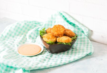 Shrimp fry is made from shrimp meat, mixed with fried dough until golden, crispy, appetizing. Served in a wooden cup, decorated with lettuce With thick sauce. Placed on a green checkered tablecloth.
