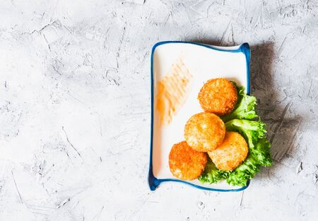 Shrimp fry is made from shrimp meat, mixed with fried dough until golden, crispy, appetizing. Served in a beautiful ceramic plate, decorated with lettuce With thick sauce. Placed on a rough texture grey surface.copy space. Reklamní fotografie - 131899475
