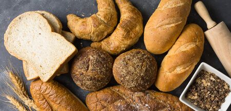 Many types of bread, including croissants, whole wheat rolls, whole wheat bread, all baguette, placed on a dark gray floor With rolling dough, whole wheat cup and decorated wheat grains