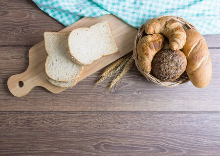Many types of bread, including croissants, whole wheat rolls, whole wheat bread, on a wooden cutting board and wicker baskets. All placed on wooden floors and tablecloths. Decorated with wheat grains.