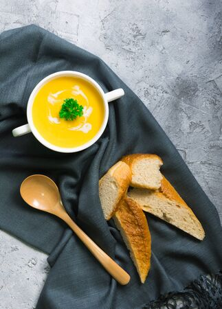 Pumpkin soup packed in a white ceramic cup. Serve with baguettes placed on a dark gray tablecloth along with a wooden spoon. Everything is laid on a white uneven floor.