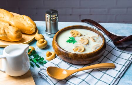 Mushroom soup packed in a wooden bowl Serves with baguettes placed on a tablecloth. Complete with pepper jar, cream cup, champignon mushrooms, wooden spoon and ladle on the blue tabletop.