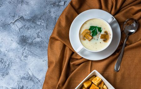 Champignon mushroom soup in a serving soup bowl with croutons put on a brown tablecloth On a rough gray surface. Reklamní fotografie - 146616906
