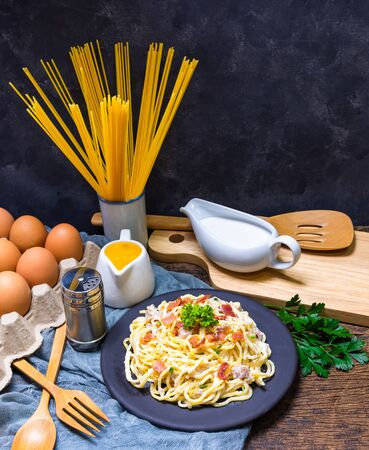 Carbonara spaghetti in a black plate, complete with ingredients and cooking tools including pasta, cream, eggs, olive oil, parsley, pepper bottle, spatula, wooden chopping board. Everything iplace on old wooden floors and dark backgrounds