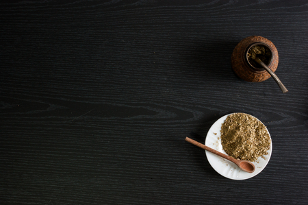 Artistic photograph of the yerba mate infusion, typical from Argentina, in a white plate, over a dark wooden background Imagens