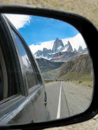 a close view of the fitz roy from the car mirror with the sky at the background