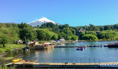 View of Villarrica Lake and the eponymous volcano of the city of Pucon in Chile, behind the trees and mountains from the road with a natural window of branches and leafs