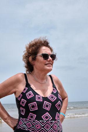 a portrait of a happy old woman on swimsuit on the beach of Solanas, Punta del Este, Maldonado, Uruguay