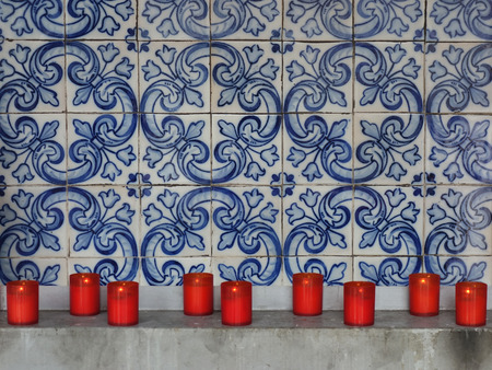 Red firing candles in catholic church on a background of Portuguese tiles.