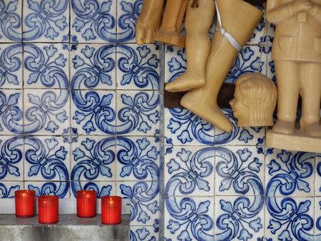 Wax votives (head, foot, leg, hand, child, baby) in catholic church on a background of Portuguese tiles.