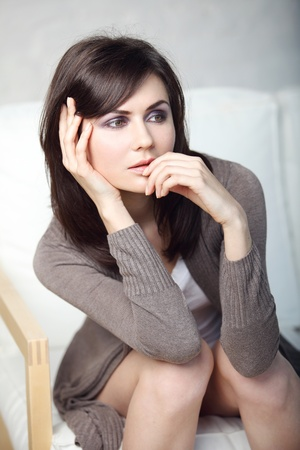 beautiful thoughtful girl sits on a sofa photo