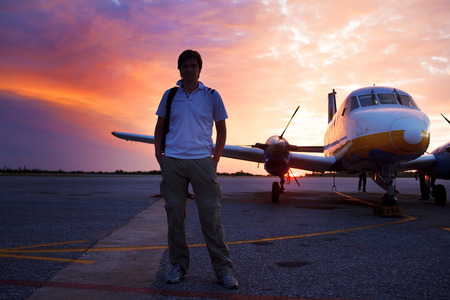 private plane: Young man on the runway in background of a small private plane Stock Photo