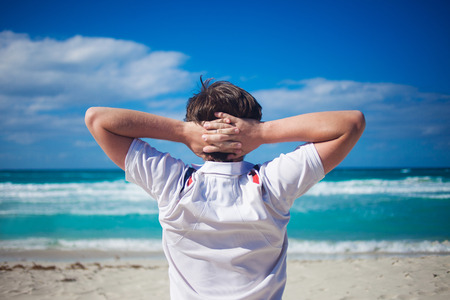 hands behind head: Handsome young man  against bright beach background, relaxes his hands behind  head Stock Photo