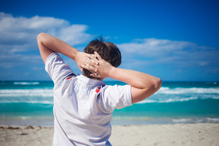 hands behind head: Handsome young man  against  beach background, relaxes his hands behind  head