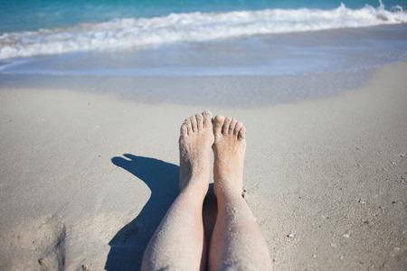 long toes: legs on the beach, female feet in  sand