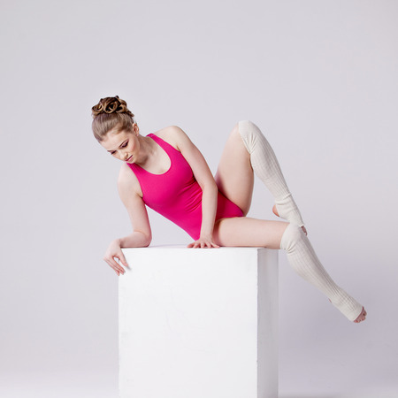 sexual position: attractive young woman gymnast on  white cube, looking down Stock Photo