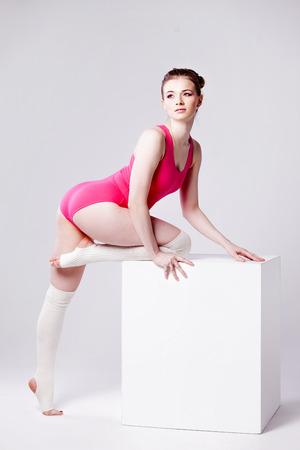 turnanzug: attraktive junge Frau Turner auf wei�en W�rfel in einem rosa Trikotanzug Lizenzfreie Bilder