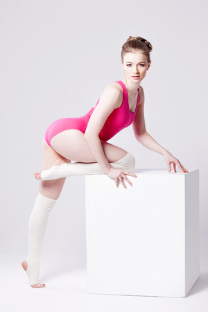 leotard: attractive young woman gymnast on  white cube, in a pink leotard