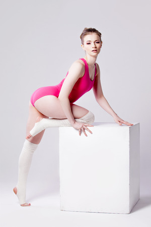leg warmers: attractive young woman gymnast on  white cube, in a pink leotard