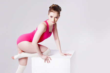 warmers: attractive young woman gymnast on a white cube,  close up