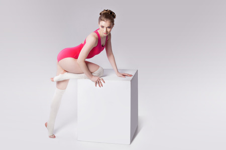 leg warmers: attractive young woman gymnast on a white cube, place for text Stock Photo