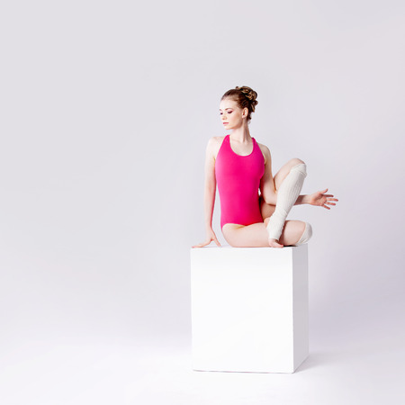 leotard: attractive young woman in pink leotard on a white cube