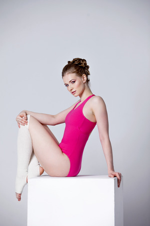sexual position: ballet dancer. attractive young woman on a white cube