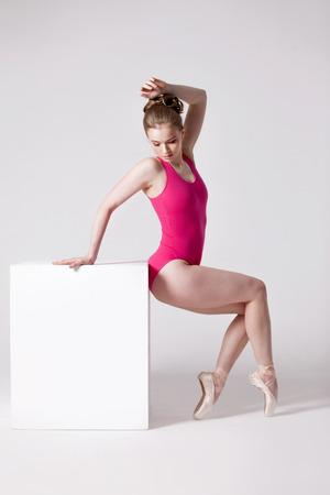 turnanzug: attraktive junge Frau in rosa Trikotanzug auf einem wei�en W�rfel
